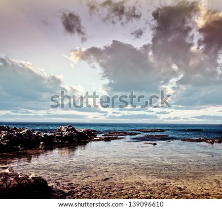 Photo of beautiful stony coast, rocky beach, dramatic sunset, cloudy sky, stunning seascape, summertime vacation, travel and tourism concept