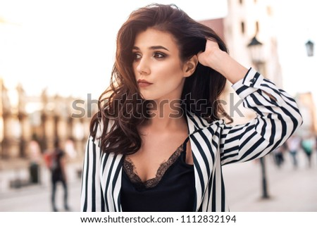 Photo of beautiful stylish brunette woman in the city ,wearing sunglasses, black and white stripes shirt. Fashion summer photo