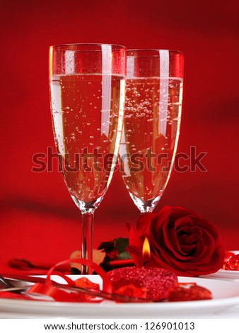 Photo of beautiful Valentine day dinner still life, two glasses for champagne, alcohol beverage, romantic drink, sparkling wine, red rose and candle, festive table setting, love concept