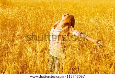 Photo of beautiful woman standing on wheat field, pretty teen girl stand on golden rye land with raised open hands and looking up, carefree young girl enjoying freedom outdoors, harvest season