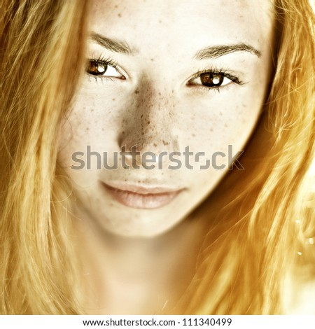 Photo of beautiful woman with freckled skin on her face