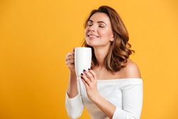 Photo of beautiful young woman standing isolated over yellow background holding cup of tea. Eyes closed.