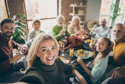 Photo of big family sit feast dishes table around roasted turkey multi-generation relatives making group selfies raising wine glasses juice in living room indoors