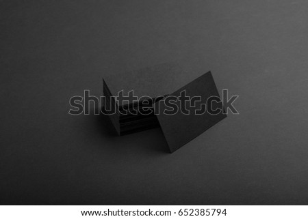Photo of black business cards. Dark template isolated on black background. For graphic designers presentations and portfolios. Business card mock-up black ob black.