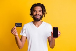 Photo of black guy hold presenting debit card telephone screen empty space wear white t-shirt isolated yellow color background