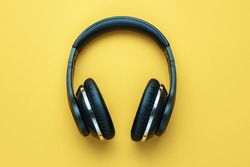 Photo of black stylish modern wire less headphone over yellow background.