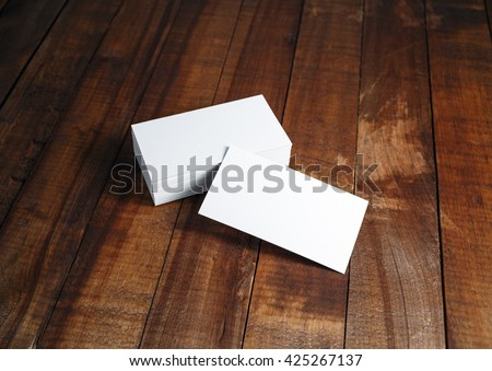 Photo of blank business cards. Blank business cards on vintage wooden table background. Template for ID. Mock-up for branding identity.