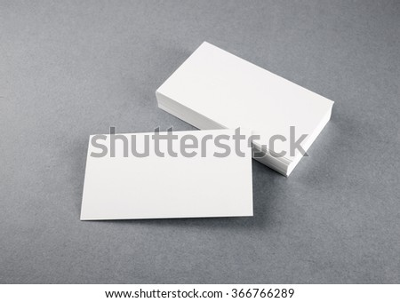 Photo of blank business cards with soft shadows on gray background. Mock-up for branding identity. Studio shot.