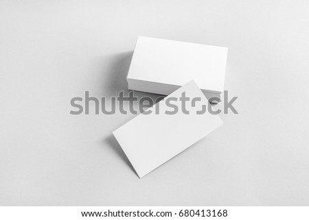 Photo of blank business cards with soft shadows on paper background. Mockup for branding identity. Studio shot.