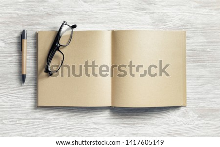 Photo of blank notepad with blank kraft paper pages, pen and glasses on light wood table background. Flat lay. #1417605149