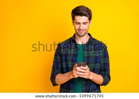 Photo of blogger guy holding telephone in hands checking instagram followers wear casual checkered shirt isolated yellow color background Stock foto ©