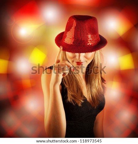 Photo of blond woman wearing stylish shiny red hat, glamour singer girl with finger up isolated on blur lights background, New Year celebration, Christmas eve, night life, dance club party