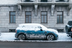 Photo of blue car covered with snow after heavy snowfall. Vehicle was not used for several days. Side of the car is stained with dirt because of passing cars. Winter and seasonal concept.