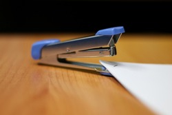 Photo of Blue stapler put on the table in office with a blurred background, stapler is a device used in schools or offices