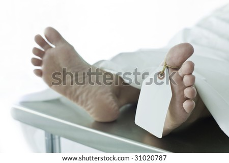 Photo of body covered with a sheet in a morgue, feet toward camera with blank tag on the big toe. Feet are clean and smooth. (body is a model)