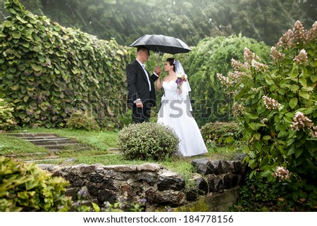 Photo of bride and groom under black umbrella at park