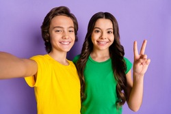 Photo of brunette happy boy and girl wear green yellow t-shirt make selfie v-sign isolated on purple color background