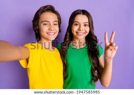 Photo of brunette happy boy and girl wear green yellow t-shirt make selfie v-sign isolated on purple color background Photo stock ©