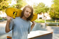 Photo of brunette skater guy 16-18 in casual wear standing with skateboard in skate park during sunny summer day