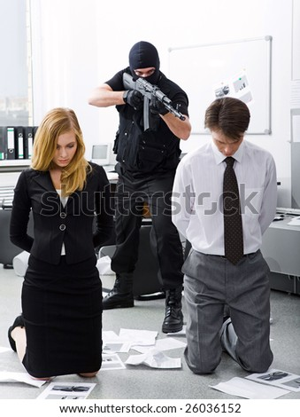 Photo of business co-workers standing on knees being aimed at by evil terrorist