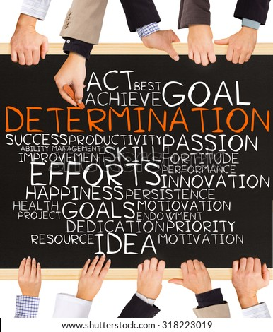 Photo of business hands holding blackboard and writing DETERMINATION word cloud