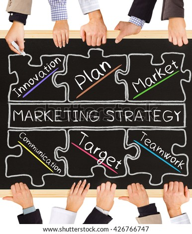 Photo of business hands holding blackboard and writing MARKETING STRATEGY concept