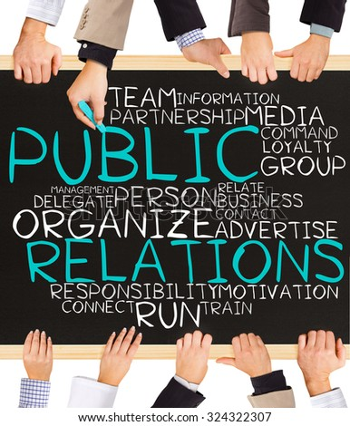 Photo of business hands holding blackboard and writing PUBLIC RELATIONS word cloud