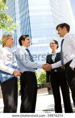 Photo of business partners handshaking at meeting in natural environment