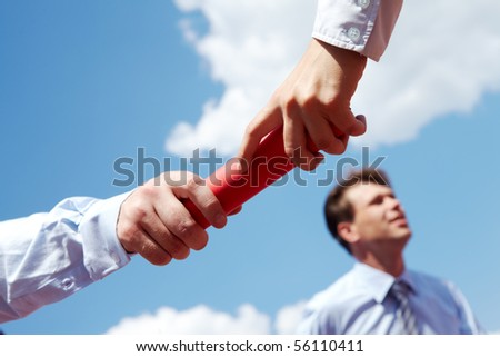 Photo of business people hands passing baton during race - stock photo