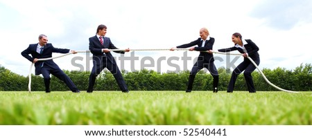 Photo of business people stretching the rope in the stadium