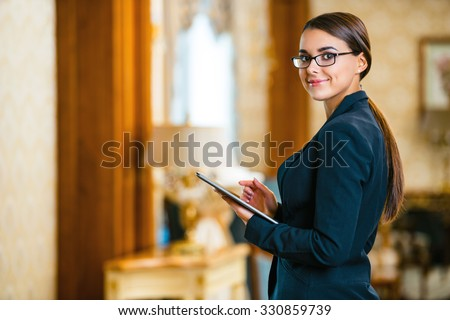 Photo of business woman in expensive hotel. Young business woman wearing suit and glasses, standing in nice hotel room, using tablet computer and looking at camera #330859739