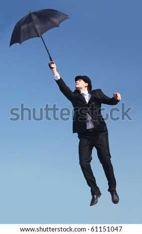 Photo of businessman flying on umbrella with blue sky at background