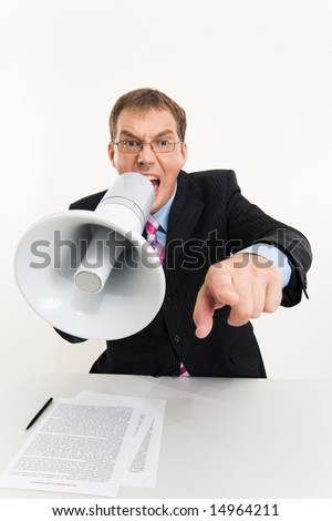 Photo of businessman sitting at the table speaking through megaphone and pointing at camera