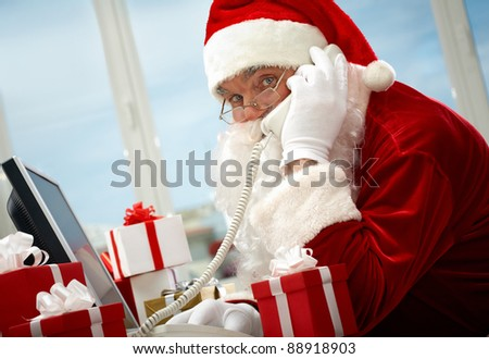 Photo of busy Santa Claus communicating by telephone
