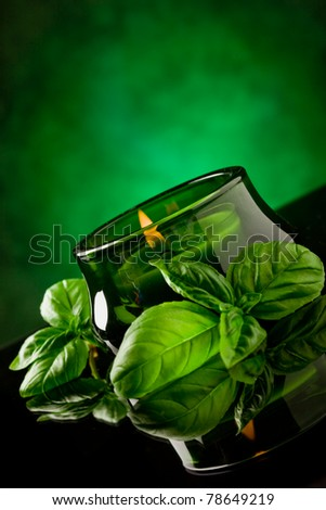 photo of candle with basil fragrance on black glass table