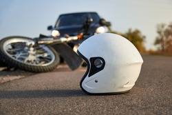 Photo of car, helmet and motorcycle on road, the concept of road accidents.
