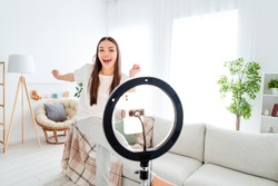 Photo of carefree funny blogger lady dance tripod phone video live broadcast wear white t-shirt pants in room indoors