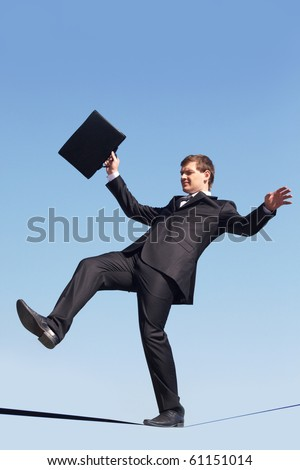 Photo of careful businessman standing on ribbon or rope running risk of falling down