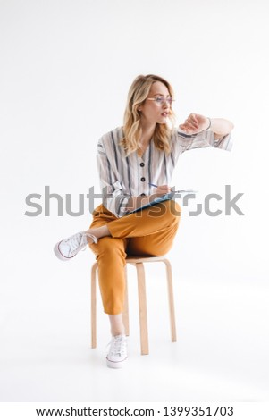 Photo of caucasian thinking woman wearing glasses sitting in chair and looking at wristwatch isolated over white background in studio