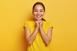 Photo of charismatic Asian female keeps hands together near chin, smiles gently, has cute expression, dark hair combed in pony tail, wears vivid yellow t shirt, entertained in awesome company