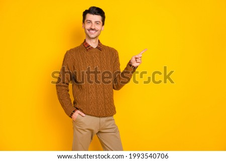 Photo of charming attarctive young man point finger index empty space hand pocket isolated on yellow color background