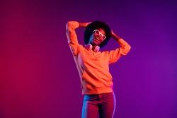 Photo of charming clubber lady dance hands head rejoice wear hoodie earphones specs isolated gradient dark background