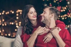 Photo of charming couple spending christmas eve in decorated garland lights room hugging piggyback near newyear tree sitting cosy sofa indoors wear red pullovers