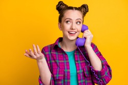Photo of charming lady two funny buns hold cable telephone handset speaking chatting friends discussing fresh gossips rumors wear casual plaid shirt isolated yellow bright color background