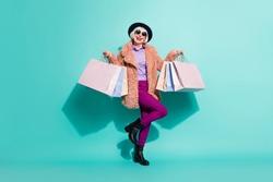 Photo of charming senior lady wear retro jacket headwear eyeglasses holding bargains isolated teal color background