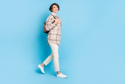 Photo of charming young lady walk wear backpack checkered coat pants footwear isolated blue color background