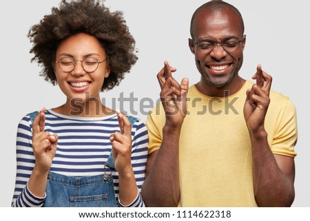 Photo of cheerful African American couple have joyful expressions, cross fingers and smile gladfully, wear casual clothes, isolated over white wall. Happy dark skinned female and male gesture indoor