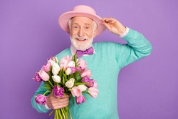 Photo of cheerful aged man arm touch headwear hold flowers toothy smile isolated on violet color background