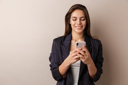 Photo of cheerful businesswoman in formal suit smiling and using cellphone isolated over white background