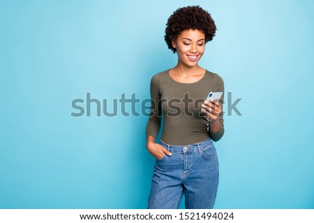 Photo of cheerful cute nice attractive black woman wearing green sweater standing confidently with her hand in pocket smiling cheerfully isolated over vivid blue color background #1521494024